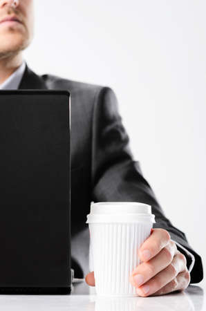 Man in business suit working on his laptop computer and drinking coffee from a take away disposable cup photo