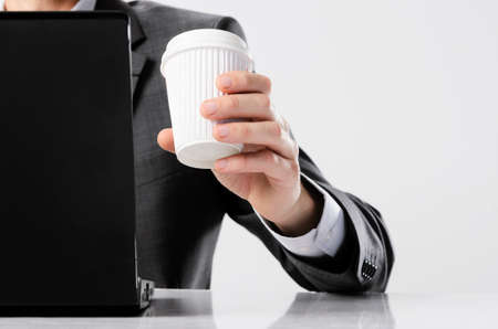 Man in business suit working on his laptop computer and drinking coffee from a take away disposable cup Stock Photo - 16483020