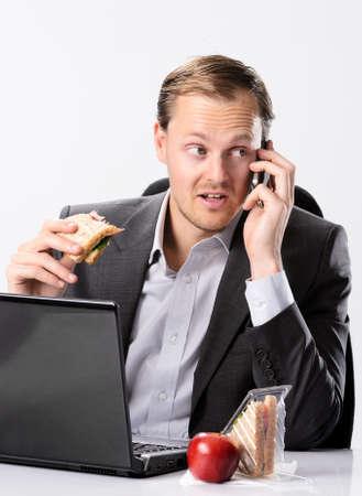 자신의 모바일 휴대 전화에서 작업 하 고 얘기하면서 바쁜 근면 한 비즈니스 남자가 자신의 책상에서 점심을 먹는다