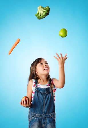 Young cute girl juggling vegetables and fruit over her head, healthy lifestyle, eating and diet concept photo