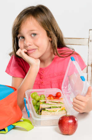 Happy smiling school girl opens her healthy lunchbox filled with fresh fruit and sandwich Stock Photo - 16599087