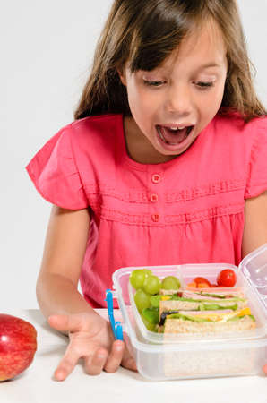 excited people: Young girl is excited about her healthy packed lunch with wholemeal ham sandwich and fresh fruit