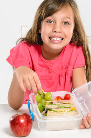 Happy smiling school girl with healthy lunchbox filled with fresh fruit and sandwich photo