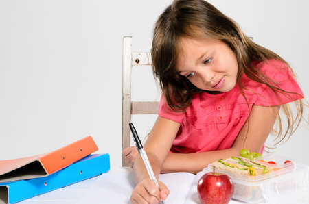 Hardworking studious cute school girl writes and does her homework with an apple and healthy packed lunch on the table Stock Photo - 16599089