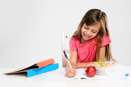 열심히 정진하는 귀여운 학교 여자가 테이블에 사과하고 건강한 도시락으로 그녀의 숙제를 기록하고 수행 스톡 사진