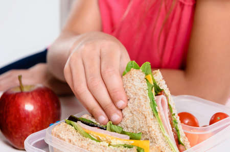packing boxes: Close up on pair of young girls hands removing a healthy wholesome wholemeal bread ham sandwich from her lunch box during breaktime Stock Photo