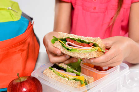 lunch box: Close up on pair of young girls hands removing a healthy wholesome wholemeal bread ham sandwich from her lunch box during breaktime Stock Photo