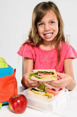 Cute young girl smiles and holds her healthy wholemeal sandwich over her lunch box and school backpack photo
