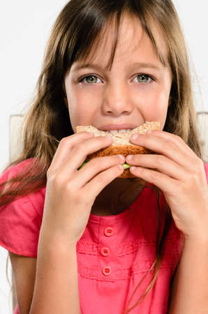Cute young girl smiling while biting eating her wholemeal sandwich photo