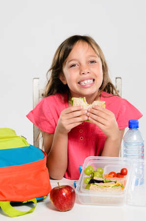 Happy smiling school girl eating her healthy lunch box sandwich with backpack and apple on the table photo