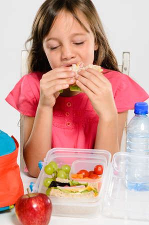 Young elementary school girl eating enjoying her healthy sandwich from her lunch box filled with nutritious food photo