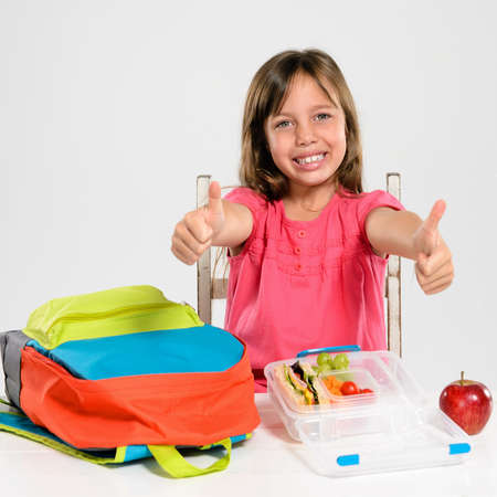Cute school girl gives the thumbs up for school and a healthy lunch box photo