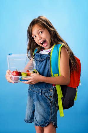 salopette: Bonne fille souriante qui tient l'�cole bo�te � lunch sain rempli de fruits frais et un sandwich sur fond bleu Banque d'images