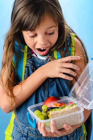 Excited young school girl holding and looking into healthy lunchbox filled with fresh fruit and sandwich on blue background photo