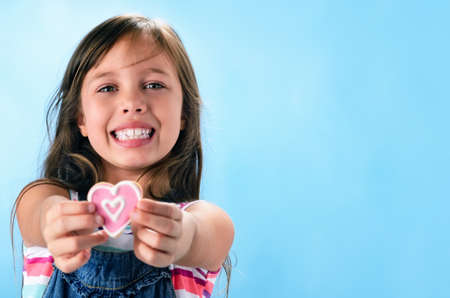 Happy smiling adorable young girl in denim dungarees holds out a pink heart shape cookie, valentines or mothers day concept Stock Photo - 16660844