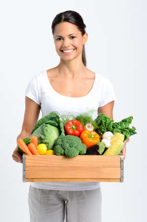 Portrait of happy young woman holding a crate full of fresh organic vegetables on grey background, promoting healthy diet and lifestyle Stock Photo - 17191867