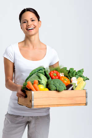 Mixed race happy young woman holding a crate full of fresh organic vegetables on grey background, promoting healthy diet and lifestyle Stock Photo - 17191868
