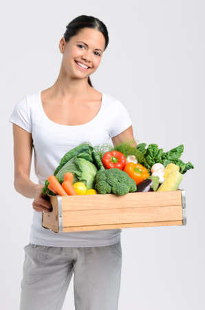 Attractive latino woman holding a crate full of fresh organic vegetables on grey background, promoting healthy diet and lifestyle Stock Photo - 17191853