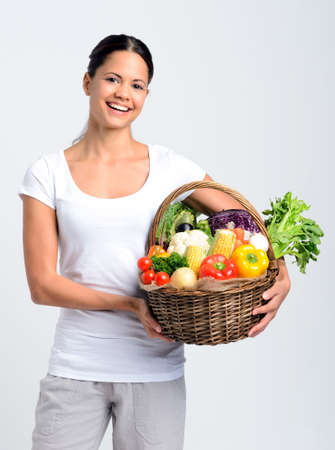 Smiling mixed race young woman holding a basket full of fresh organic vegetables on grey background, promoting healthy diet and lifestyle Stock Photo - 17191873