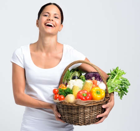 Portrait of happy young woman holding a basket full of fresh organic vegetables on grey background, promoting healthy diet and lifestyle Stock Photo - 17191855