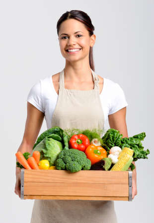 asian produce: Portrait of smiling asian woman holding a crate full of fresh organic produce on grey background, promoting healthy living, diet and lifestyle