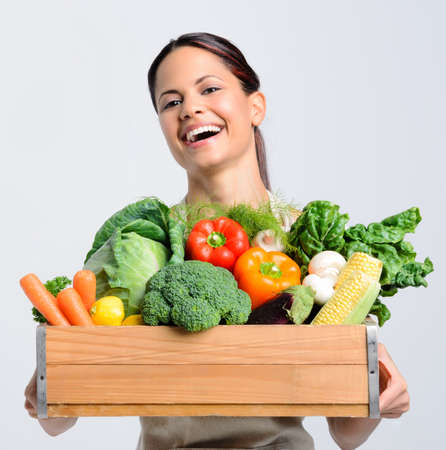Portrait of laughing happy young woman holding a crate full of fresh organic produce on grey background, promoting healthy living, diet and lifestyle Stock Photo - 17191848