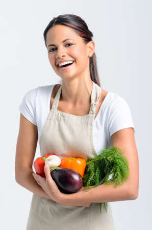 Portrait of happy young woman in apron holding fresh organic vegetables in her hands on grey background, promoting healthy diet and lifestyle photo