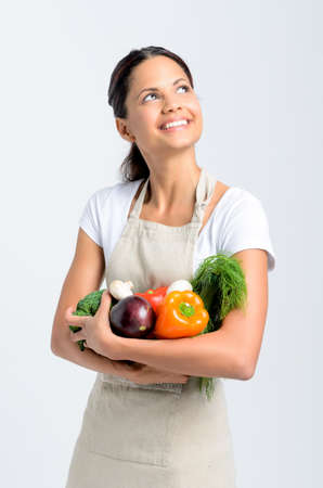 Happy mixed race woman in apron holding fresh organic vegetables in her hands and looking up on grey background, promoting healthy diet and lifestyle photo