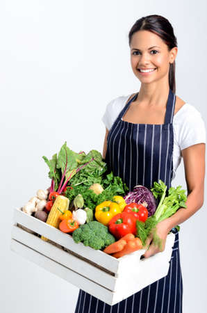 asian produce: Portrait of smiling mixed race woman chef holding a crate full of fresh organic vegetables on grey background, promoting eating seasonally and sourcing from local producers