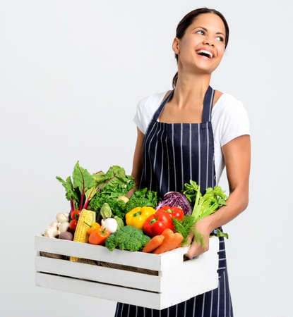 Portrait of happy young woman chef holding a crate full of fresh organic vegetables on grey background, promoting eating seasonally and sourcing from local producers Stock Photo - 17191852