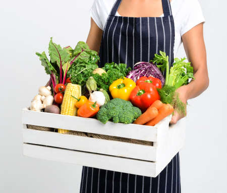 Chef holding a crate full of raw fresh organic vegetables on grey background, promoting eating seasonally and sourcing from local producers photo