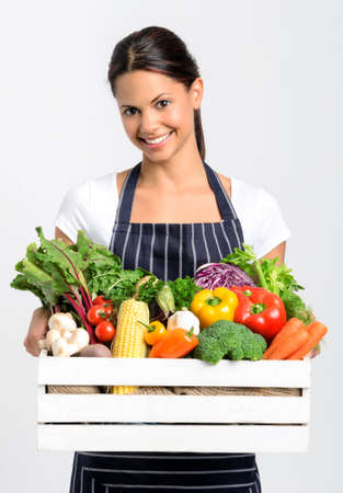 Portrait of happy indian woman chef holding a crate full of fresh organic vegetables on grey background, promoting eating seasonally and sourcing from local producers