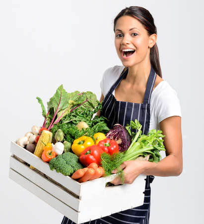 Portrait of happy young woman chef holding a crate full of fresh organic vegetables on grey background, promoting eating seasonally and sourcing from local producers Stock Photo - 17191866
