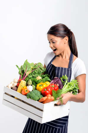 Portrait of joyful hispanic woman chef holding a crate full of fresh organic vegetables on grey background, promoting eating seasonally and sourcing from local producers Stock Photo - 17191863