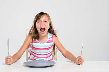 ni�a gritando: Hungry joven enojado gritando, gritando, lanza una tanrum sentado en una mesa con la placa vac�a