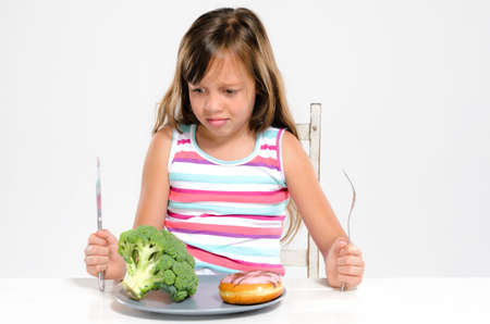 sugary: Cute young girl child making a choice between healthy broccoli vegetable and unhealthy sugary donut Stock Photo