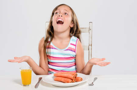 Young child protesting at the dinner table, refusing to eat her vegetable produce carrots, meal time problems concept Stock Photo - 17191860