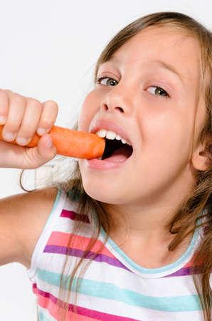 boca abierta: Sonriente ni�a feliz comiendo una zanahoria cruda fresca, concepto de alimentaci�n saludable