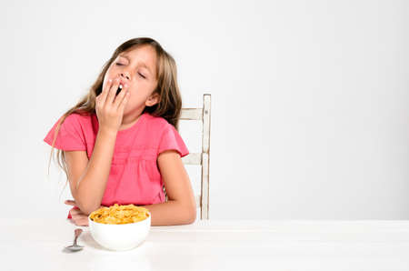 Adorable young girl is sleepy and yawns at the breakfast table with a bowl of nutritious healthy cornflake cereal Stock Photo - 17191857