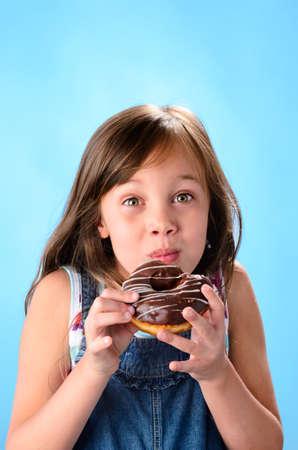 달콤한 귀여운 소녀 파란색 배경에 초콜릿 글레이즈 도넛을 먹고 즐기는 스톡 사진