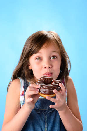 Sweet cute girl eating and enjoying a chocolate glazed donut , on blue background photo