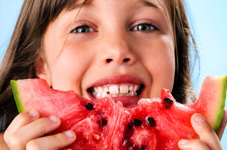 Cute smiling young girl with fresh juicy watermelon summer fruit, healthy living and diet concept on blue background photo