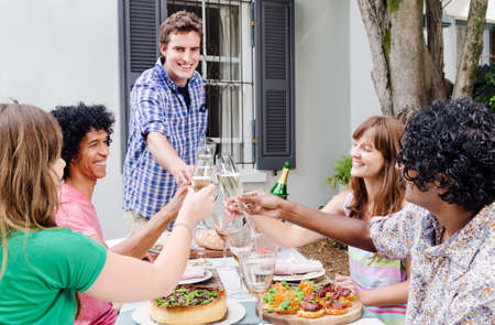 Group of friends gathered and sharing a toast of champagne, celebrating a special occassion in a casual garden outdoor setting with delicious platters of food on the table
