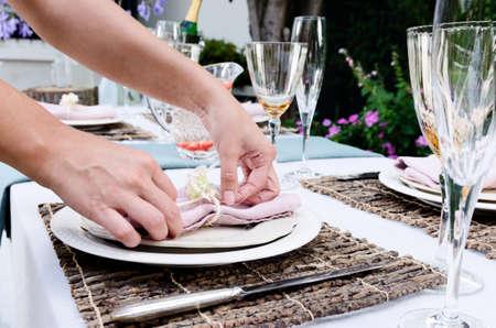 단순 소박한 컨트리 스타일 테이블 설정에 대한 냅킨에 대한 최종 조정을하는 손의 쌍, 파티 캐주얼 야외 정원 설정에서 수집 스톡 사진