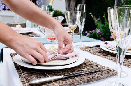 Pair of hands making final adjustments to a napkin for a simple rustic country style table setting, a party gathering in a casual outdoor garden setting photo