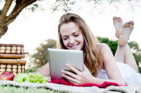 Beautiful young woman with tablet computer in park relaxing and reading with fruit and picnic basket Stock Photo - 17686973