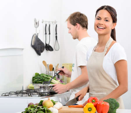 asian cooking: Happy smiling woman in kitchen with fresh produce vegetables preparing for a healthy meal, with partner husband cooking in background