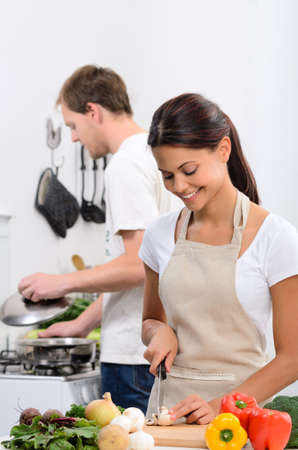 vegetables young couple: Happy couple cooking in the kitchen, beautiful wife slicing vegetables
