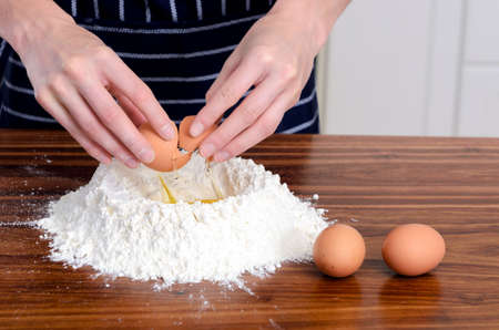 Close up of chef's hands with plain flour well and eggs in preparation process for baking, cooking, pastry making photo