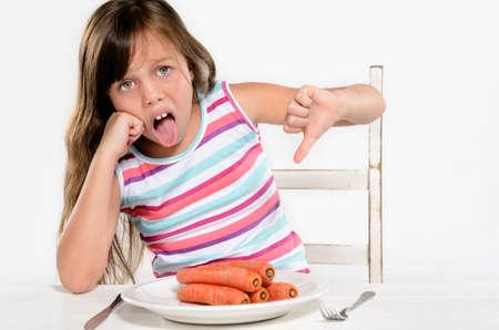 lengua afuera: El ni�o mira con asco vegetal, neg�ndose a comer y pegue la lengua fuera Foto de archivo